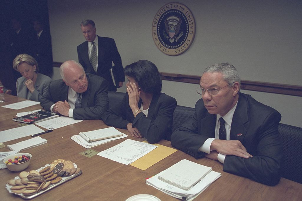 Three of the president's advisors sit in front of the government seal with serious expressions. Cheney and Rice are leaning toward each other as they talk. Powell, with arms folded on the table, appears to be listening to someone across the table.