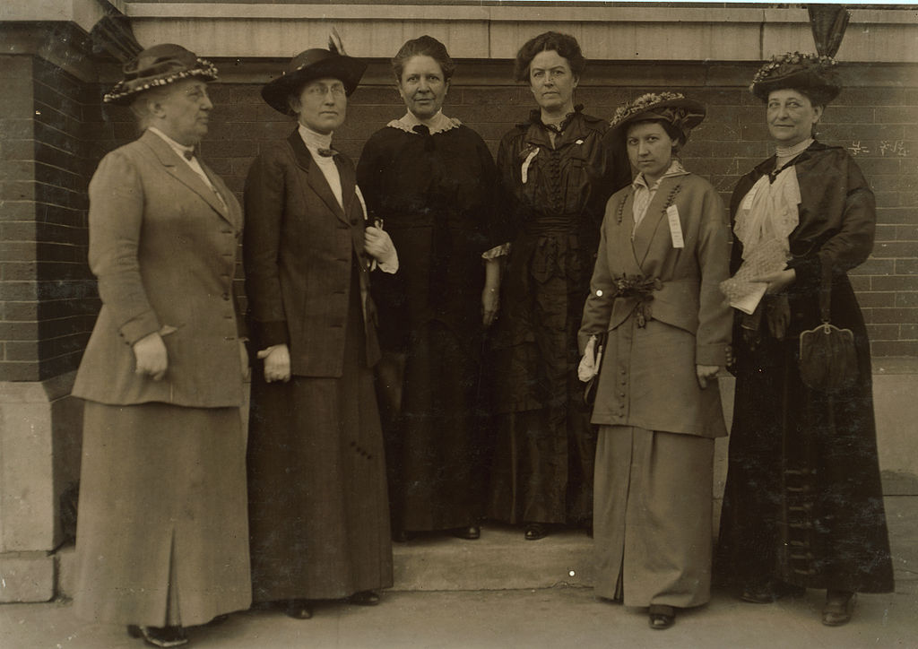 Six women in early 20th century professional dress stand on the step by a brick building.