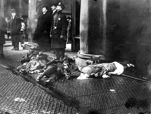 The bodies of four lifeless women lay strewn on the sidewalk. A policeman stands by the bodies. He and two others look upward while another man looks toward the bodies from several yards away.