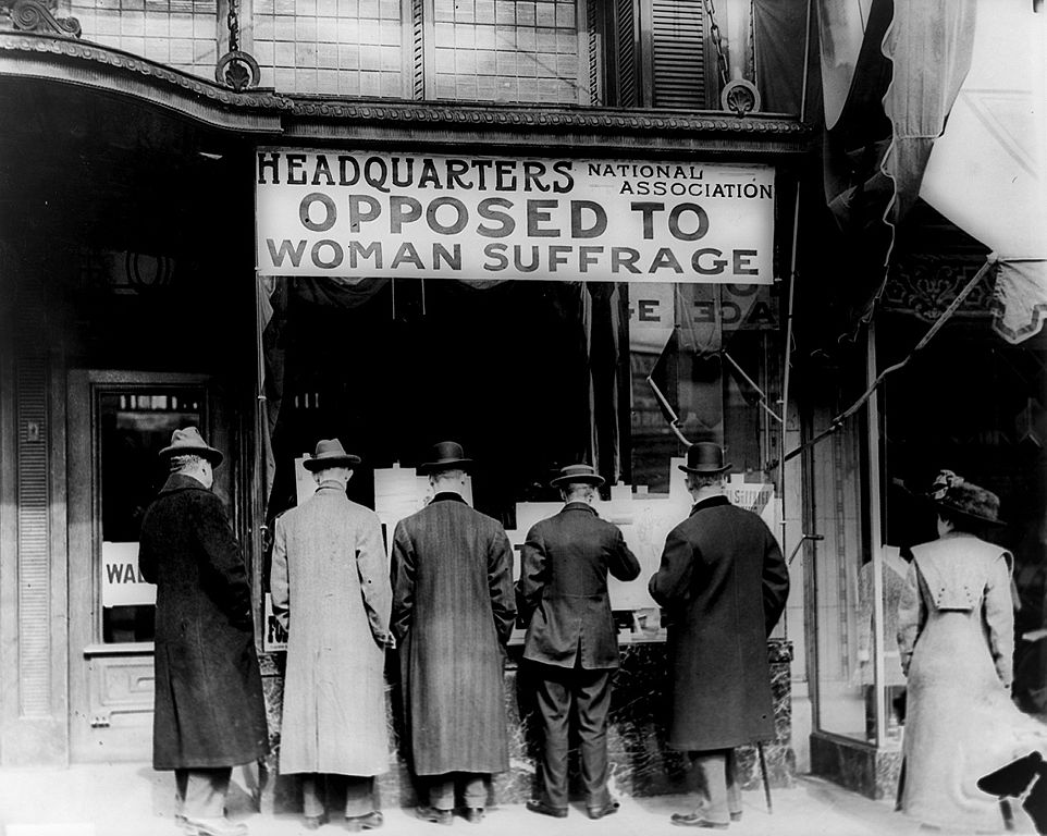 Photograph shows men looking at material posted in the window of the National Anti-Suffrage Association headquarters; sign in window reads 'Headquarters National Association Opposed to Woman Suffrage'.