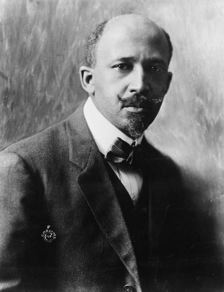 Portrait of Du Bois facing right and looking intently into the camera. In this photo, he has a short goatee, an upturned mustache, and a bowtie.
