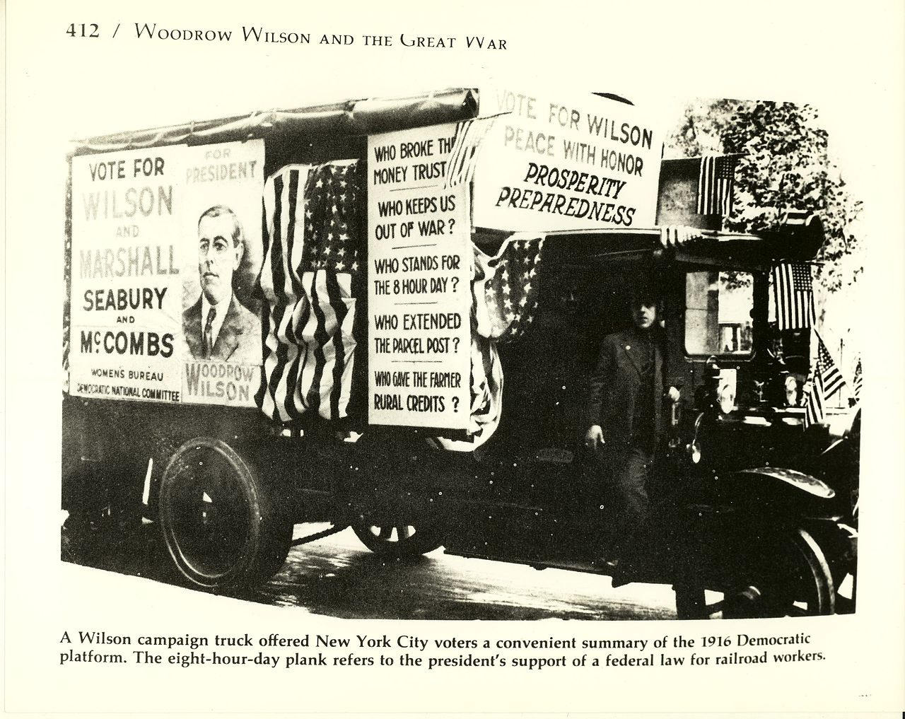 Early 20th Century truck with multiple placards attached. Placards urge voters to Vote for Wilson.