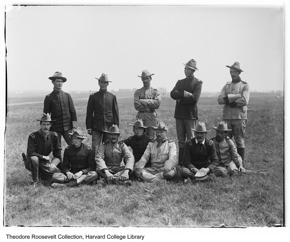 Twelve men pose in ten-gallon hats in a field of grass.