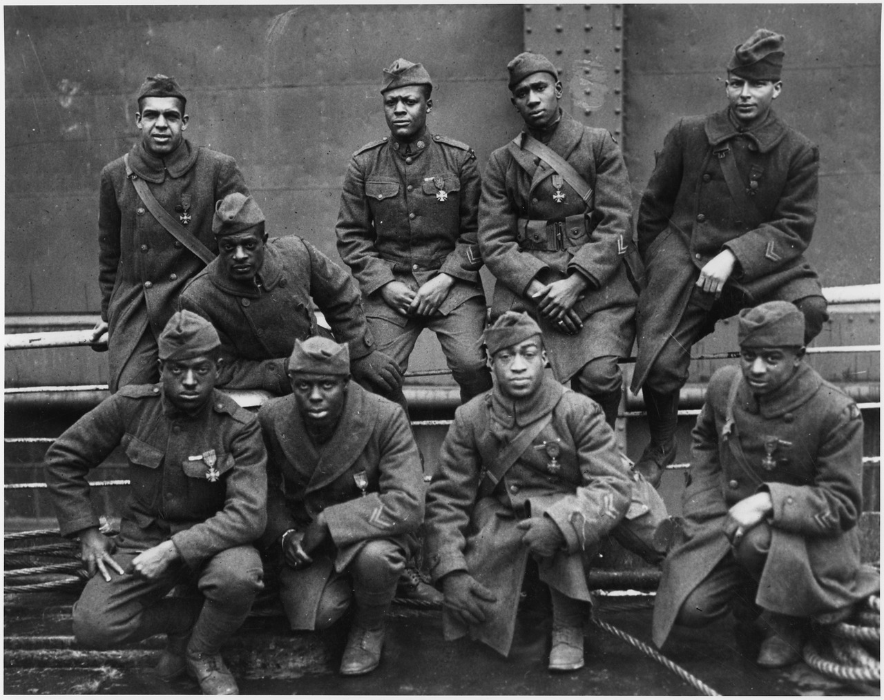 Nine young African American soldiers, each wearing a square-crossed medal on two crossed swords hanging from a ribbon.