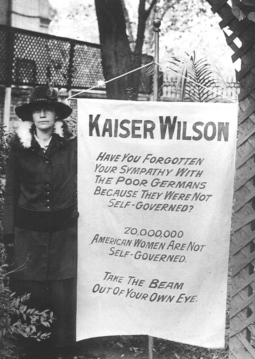 Photograph of Virginia Arnold posing with banner: 'Kaiser Wilson Have you forgotten your sympathy with the poor Germans because they were not self-governed? 20,000,000 American women are not self-governed. Take the beam out of your own eye.'