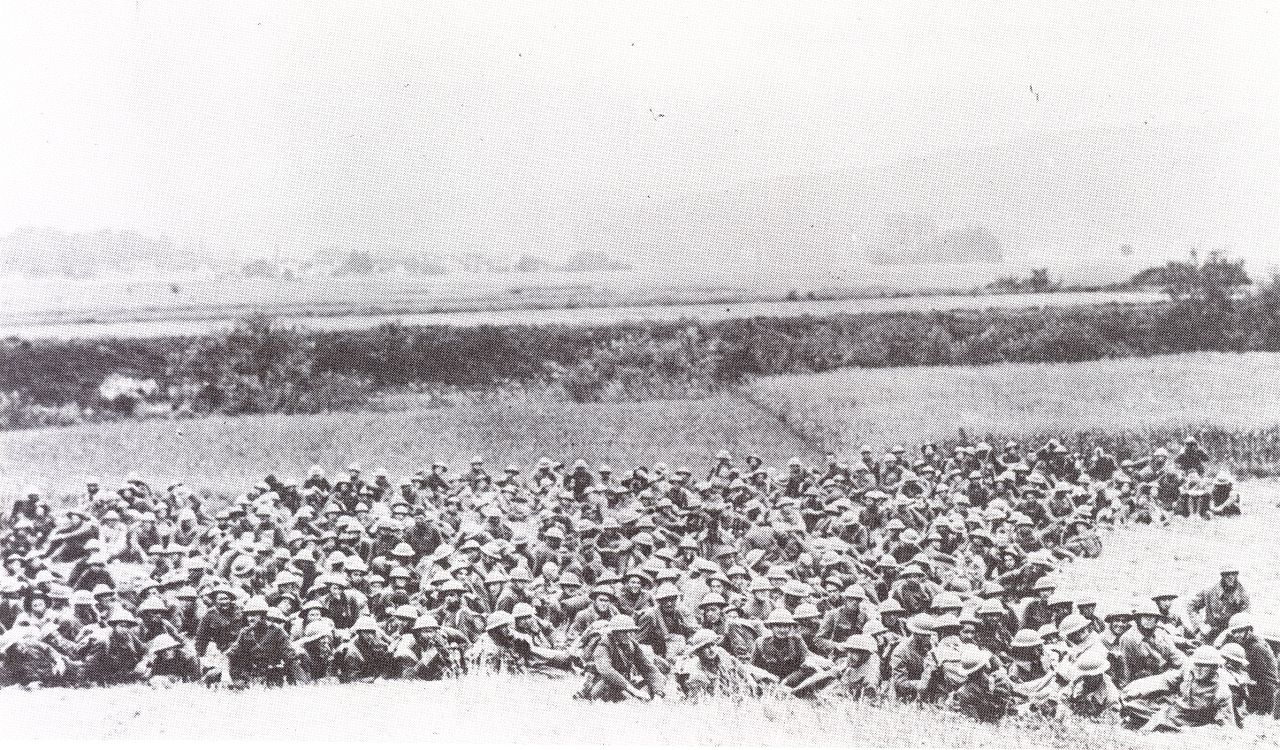a few hundred men sit and lie in a field.
