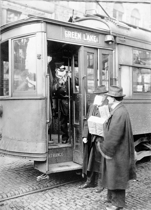 Two men waiting to board a street car. The conductor holds out his hand to prevent an unmasked man from becoming a passenger.