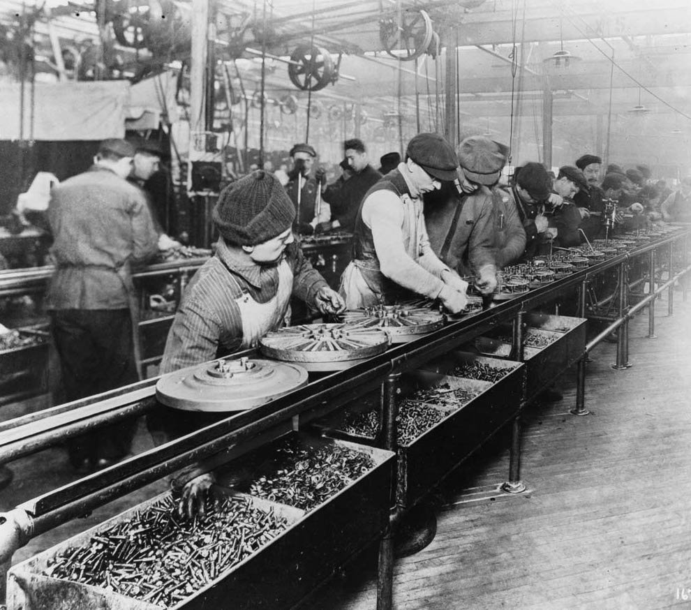 A long line of workers stand at a conveyor belt that is waist-high. The workers are putting screws into flywheels as the flywheels move down the conveyor belt.