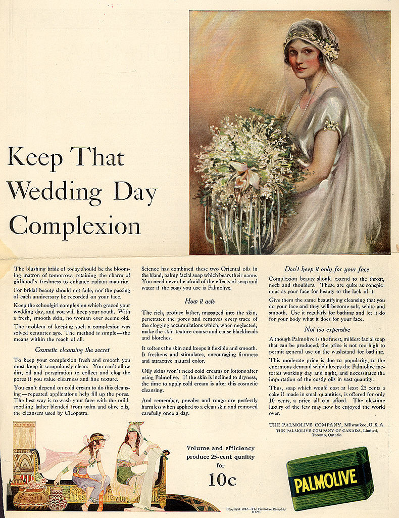 """An advertisement headlined """"Keep That Wedding Day Complexion"""" features an illustration of a rosy-cheeked, elaborately dressed bride. An image of Palmolive soap is shown alongside a lengthy description of the soap's benefits. At the bottom, to illustrate that the soap contains oils used by Cleopatra, an image depicts two rosy-cheeked, white women dressed in flowing garments and seated in a room whose décor is reminiscent of ancient Egypt."""