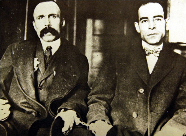 Two men sit facing the camera. They are handcuffed at the wrist.