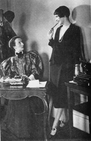 A staged and posed joke photo of a young lady in prim 1890s clothes sitting at a desk pretending to be startled by a 1920s flapper standing next to her.