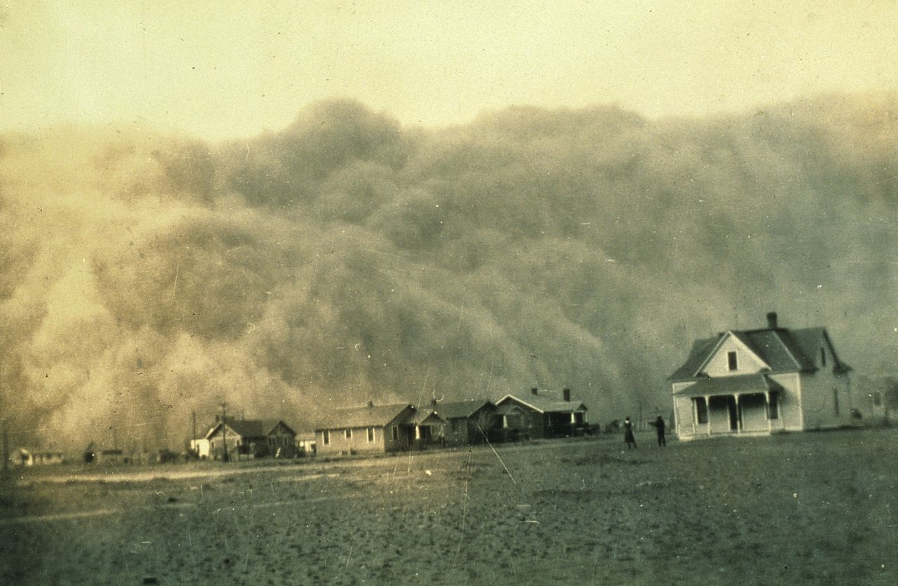 A large dust storm rising hundreds of feet into the air rolls toward houses set on flat ground.