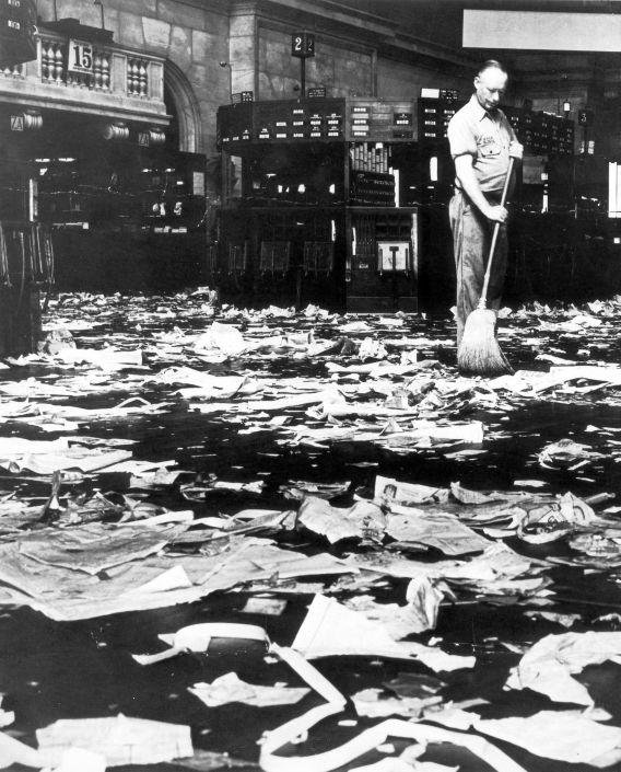 A man begins to sweep the floor of a large room littered with paper trash.