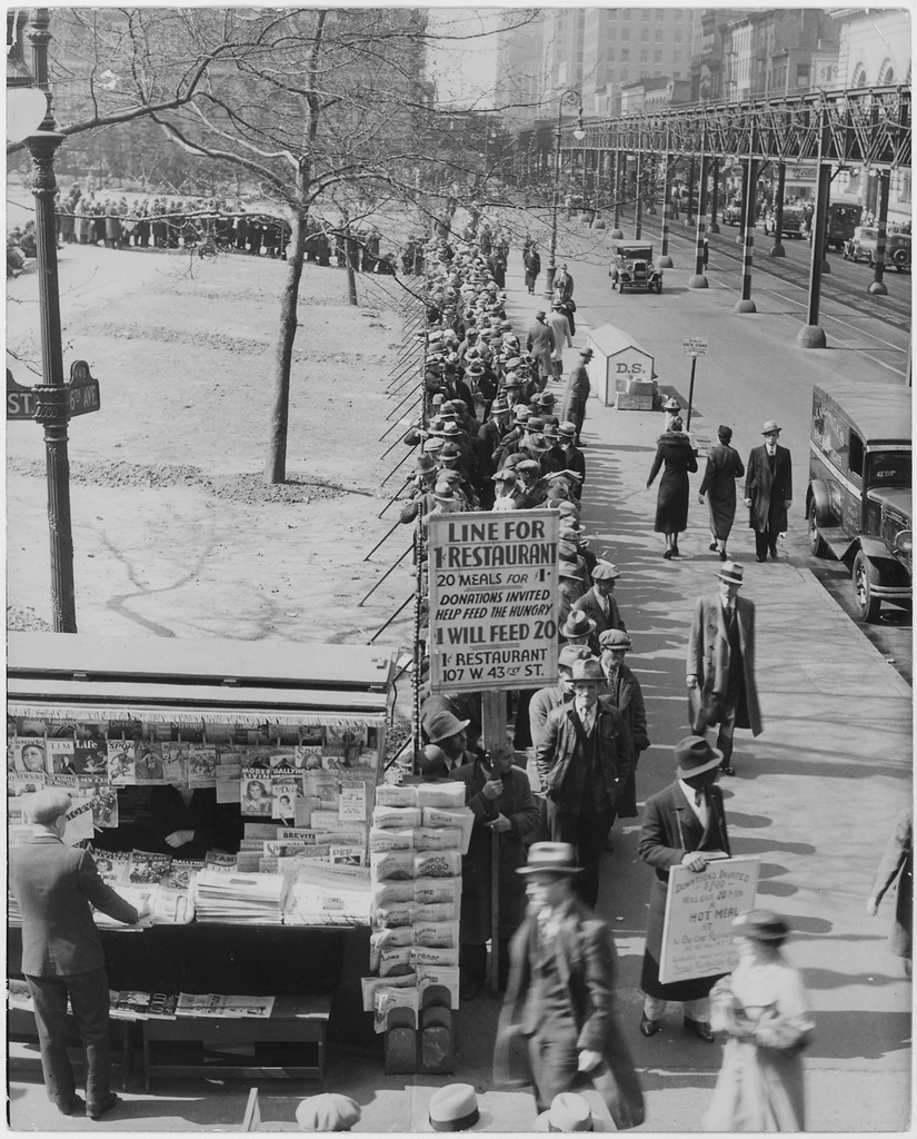 Black and white image of a bread line stretching around the corner of a city block. A large sign in the front reads: 'Line for 1 cent restaurant. Twenty meals for one dollar. Donations invited - help feed the hungry. One dollar will feed twenty.'