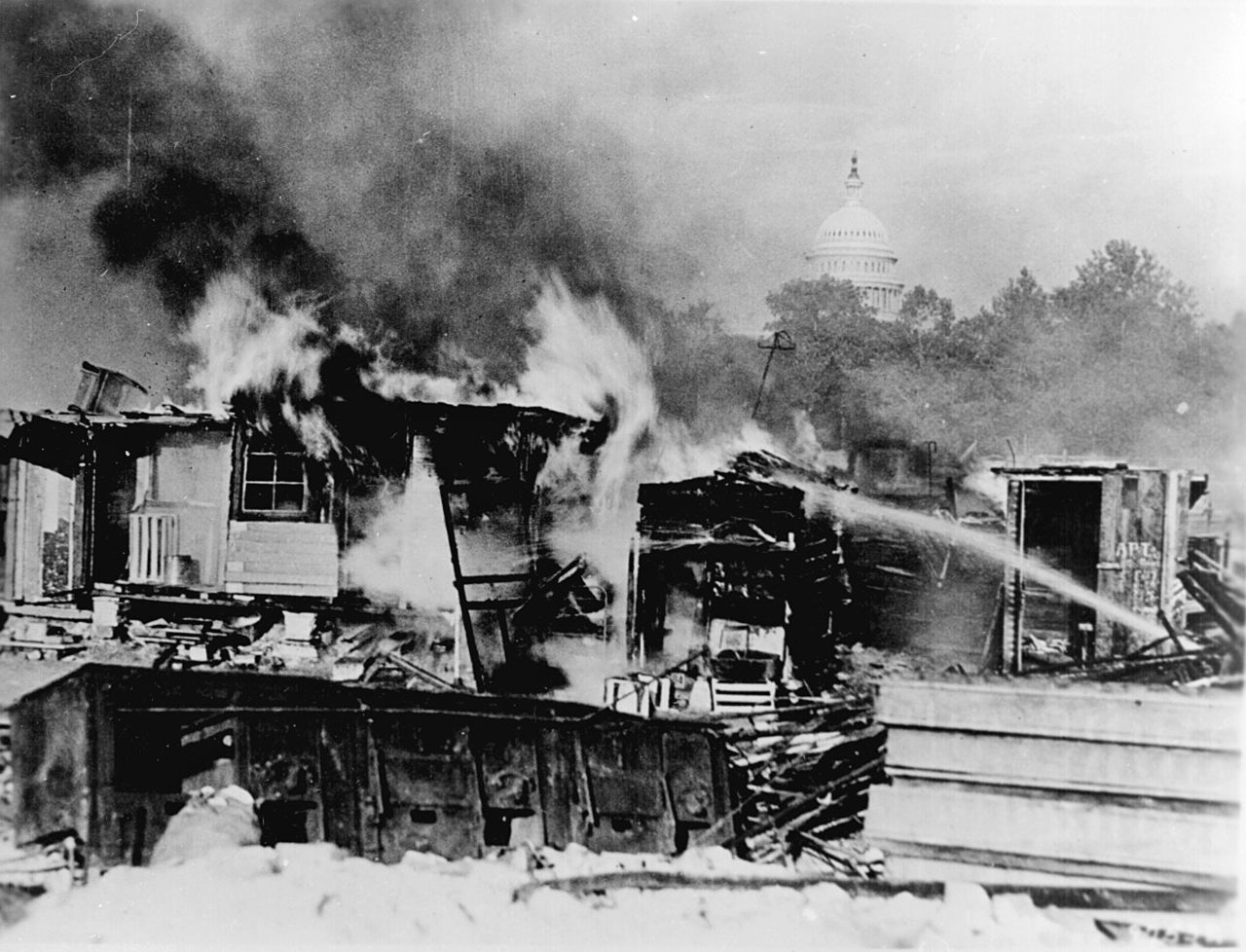 Wood and paper shacks in flames. A gush for firefighter water streams from the right. The capital building is visible through the smoke in the background.