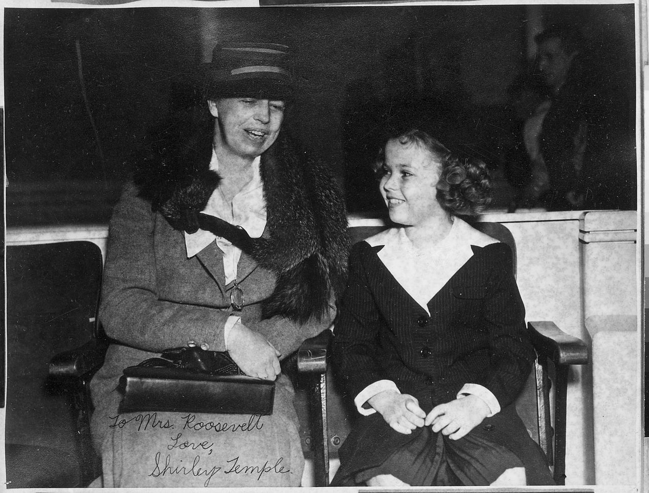 Mrs. Eleanor Roosevelt sits next to a 10-year old Shirley Temple. Both are smiling.