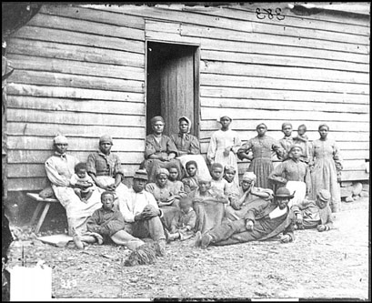 A group of 22 men, women, and children are posed standing or seated in front of an unpainted clapboard house.