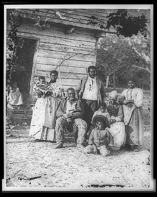 A three-generation family of eight African Americans pose by an unpainted wooden house.