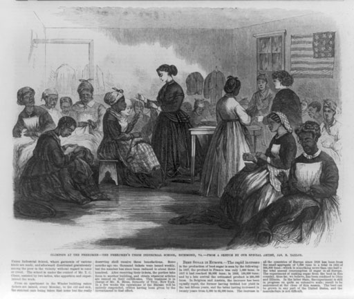 A group of about 20 African American women sew various garments in consultation with two white women.