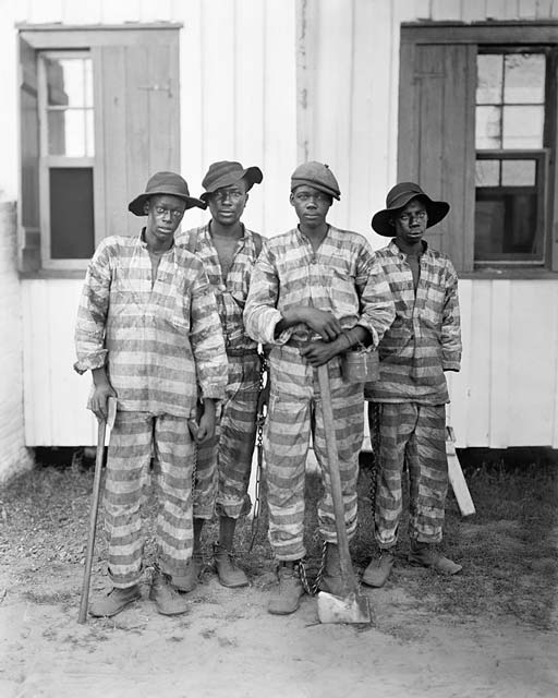 Four African American convict laborers, two of whom are holding axes which were used to harvest timber.