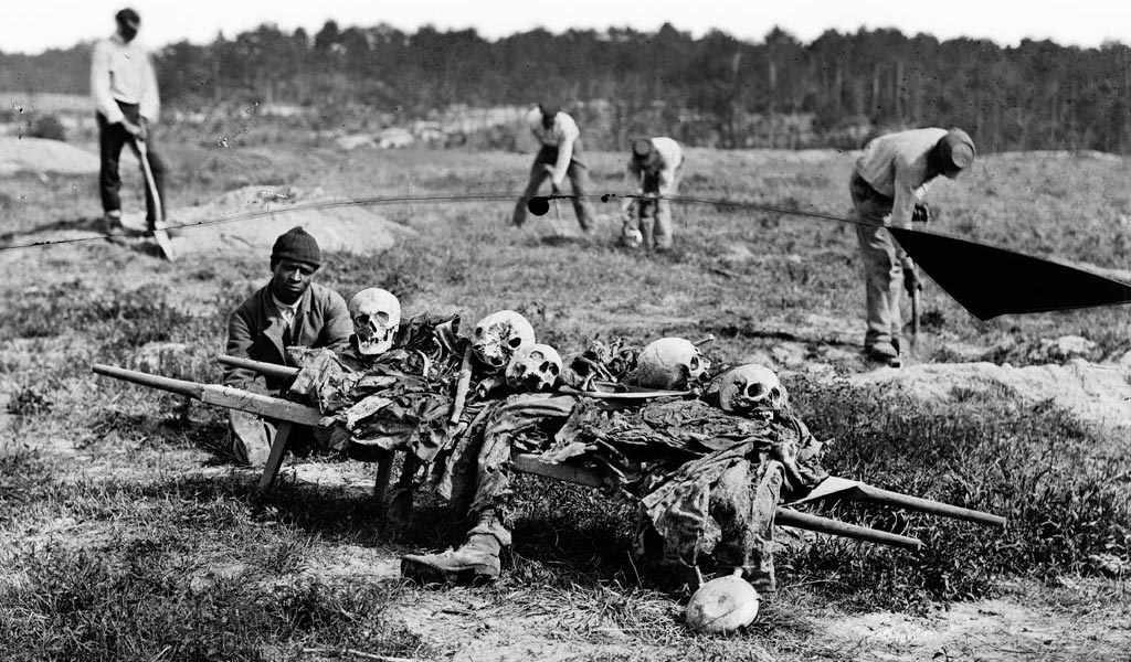 African-American men collecting bones of soldiers killed in battle at Cold Harbor, Virginia.