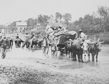 A wagon pulled by 2 oxen on a muddy road. The wagon holds several African Americans. Behind them union soldiers on horse and on foot mill about.