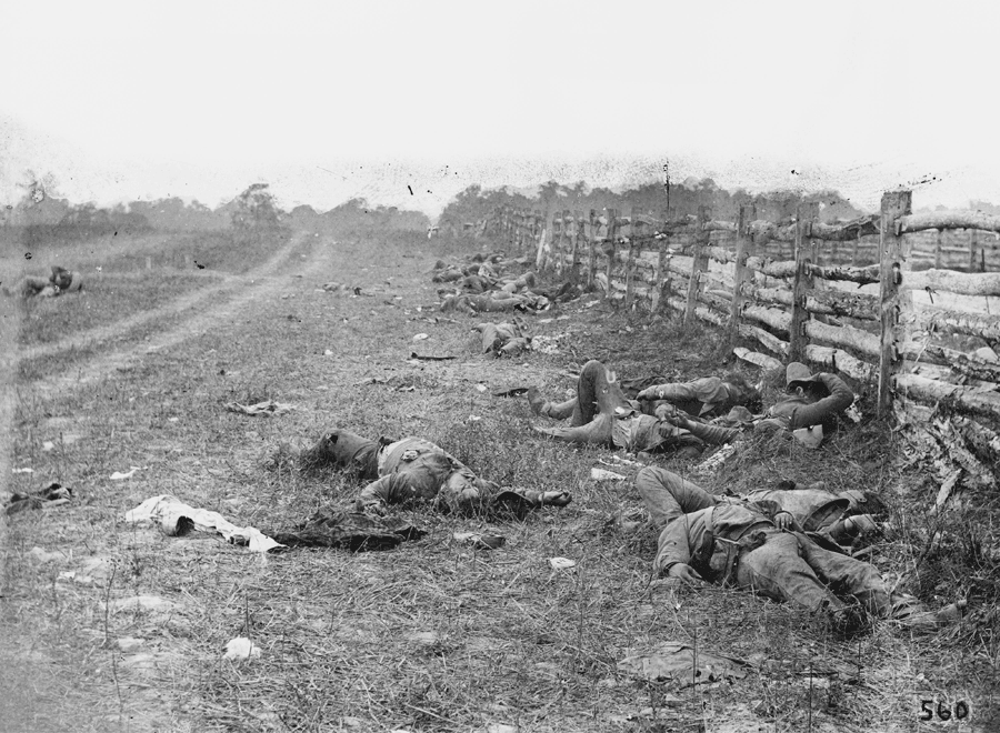 Men in uniform lie haphazardly between a stock fence and a dirt road.