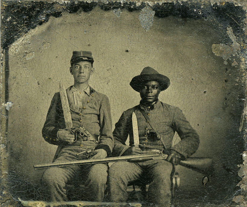 A white sergeant posing in uniform with one of his family slaves who also appears in uniform. Both men hold Bowie knives. The white man holds a revolver and the African American man lays a rifle over his and his owner's lap.