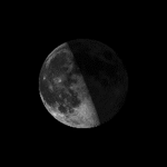 The left half of the lighted side of the moon is visible