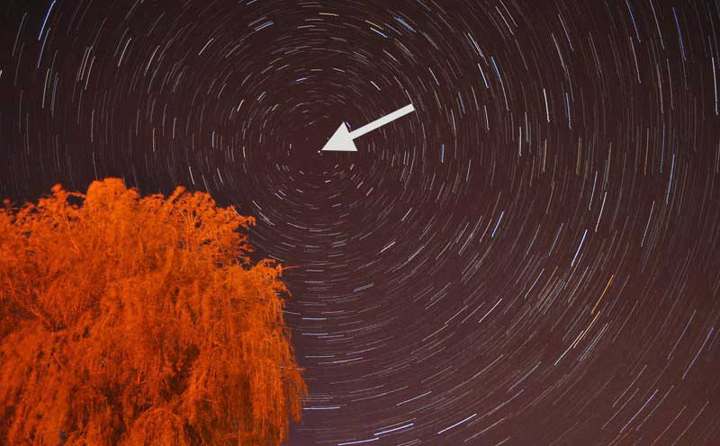 A star trail photograph. Polaris — a yellow star — is at the very center of the photo, indicated by the arrow.