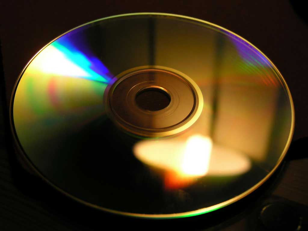 The bottom of a CD is shown with colors illuminated by a light reflection.