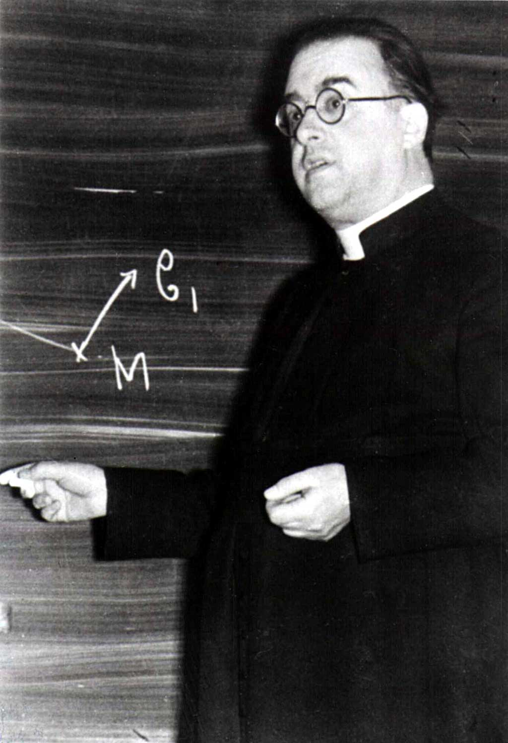 Georges Lemaître is shown writing on a chalkboard.