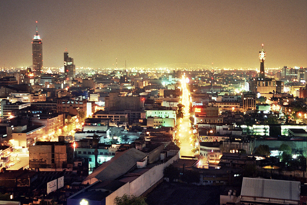 Mexico City at night with glowing streets and sky is shown.