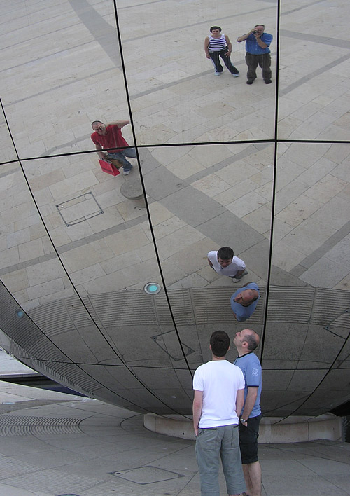 people are shown standing beneath a giant mirrored sphere While looking at their reflections.