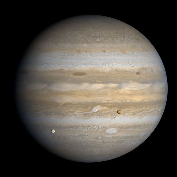 A Voyager 1 image of Jupiter, showing the many storms in the Jovian atmosphere, as well as two of Jupiter's moons (Europa on the left, Io on the right).
