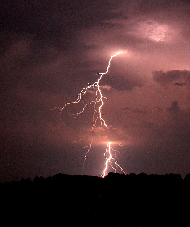 lightning is shown striking the ground in the distance.