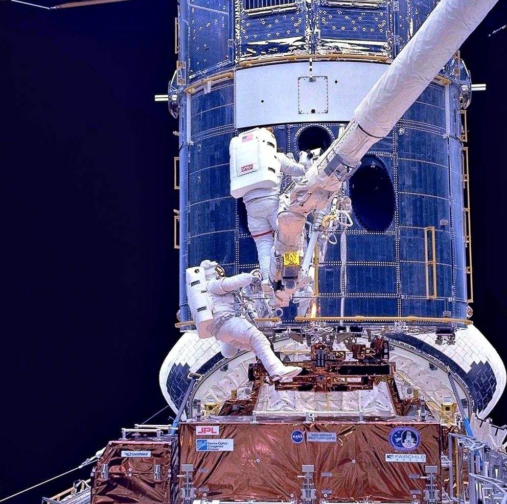 Two astronauts are shown while working on the HST while in space.
