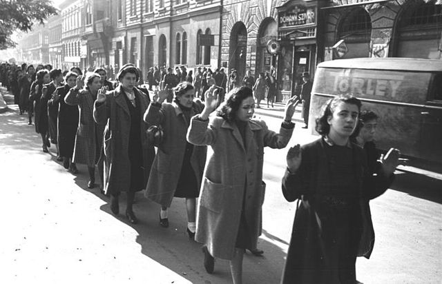 Black and white photo of captured Jewish women with hands raised in Budapest, Hungary, October 1944.