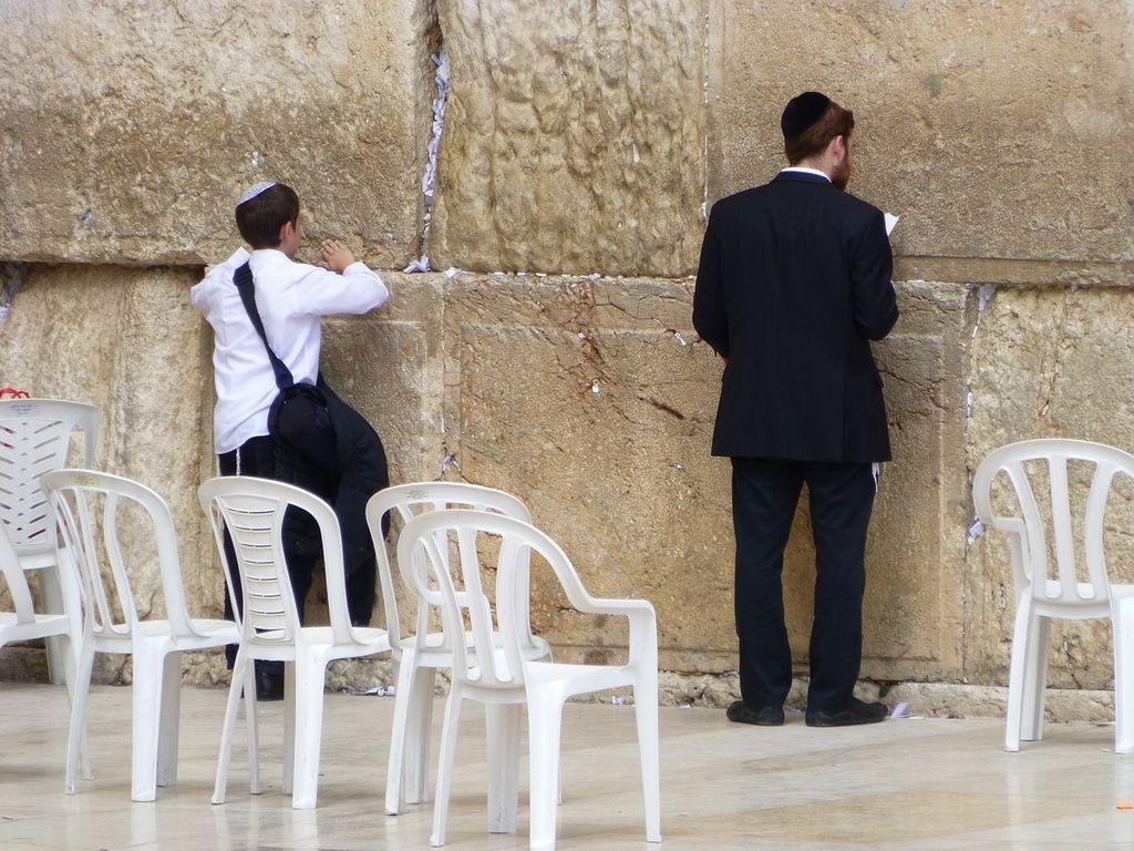 Young Jewish boy and man each wearing a yarmulke pray at the Wailing Wall in Jerusalem.