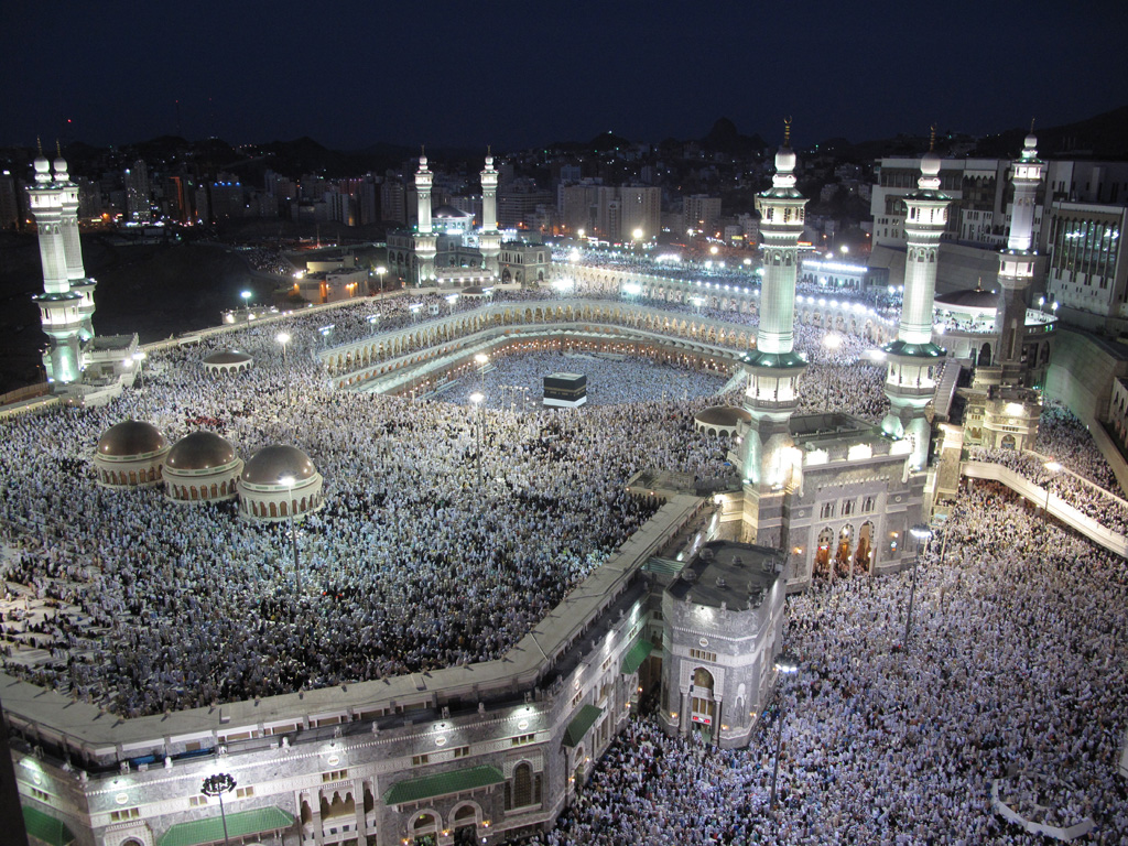 Thousands of Muslim congregants dressed in white converge at the Grand Mosque in Mecca. Moving in a circular pattern, worshippers make their way to the interior of the Mosque where the rectangular Ka'aba sits.